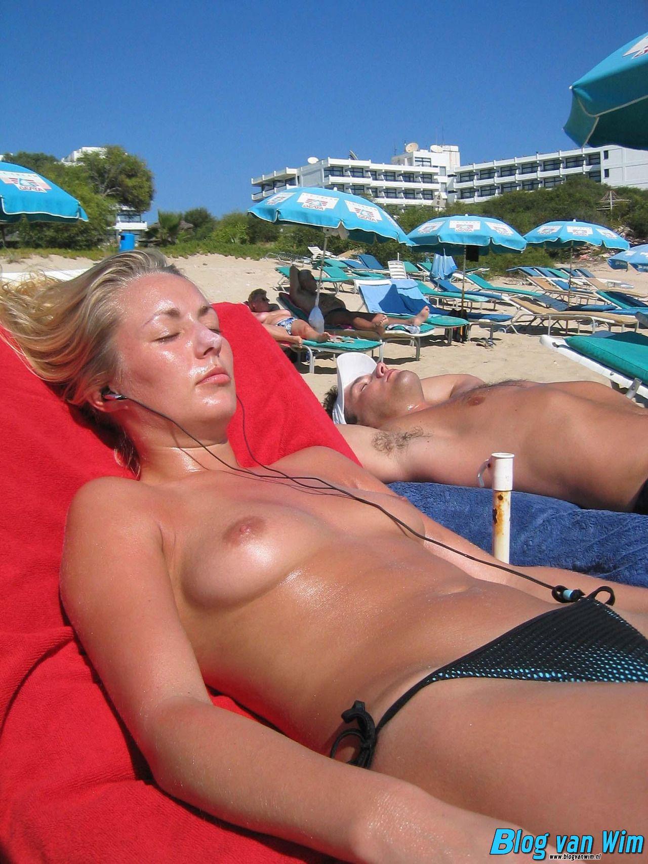Mooie gebruinde dame is topless aan het zonnen!