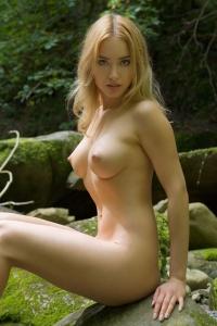 Beeldschone blondine met mooie borsten zit naakt in de tuin!